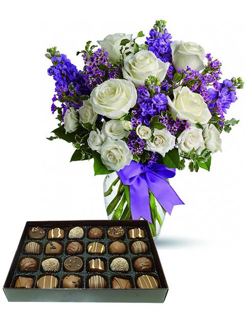 rose bianche e fiori viola con cioccolatini